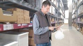 L'homme travaille dans un entrepôt de stockage a utilisé une tablette photos libres de droits