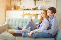 L'homme ?treint la dame s'asseyant sur le sofa et embrassant dans la cuisine photo stock