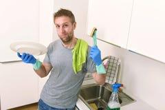 L'homme triste et frustrant faisant la vaisselle et faisant à l'évier de cuisine à la maison le sentiment propre a fatigué Image libre de droits
