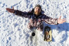 L'homme triste européen barbu prie tandis qu'il se mettant l'échouer à la pêche d'hiver photographie stock