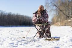 L'homme triste européen barbu prie tandis qu'il se mettant l'échouer à la pêche d'hiver photographie stock libre de droits