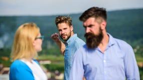 L'homme a trouvé ou a détecté l'amie le tricher marchant avec un autre homme Ami complètement des regards jaloux soupçonneusement Photo libre de droits