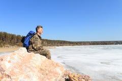 L'homme a un repos sur des pierres. Photos libres de droits