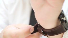 L'homme utilise des montres avec la courroie en cuir de Brown banque de vidéos