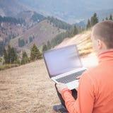 L'homme utilise l'ordinateur portable à distance à la montagne Images stock