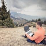 L'homme utilise l'ordinateur portable à distance à la montagne Image libre de droits