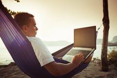 L'homme utilise l'ordinateur portable à distance photos libres de droits