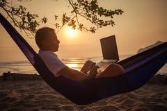 L'homme utilise l'ordinateur portable à distance images libres de droits