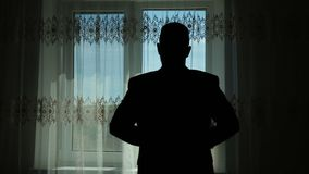 L'homme utilise une veste devant un contraste de fenêtre clips vidéos
