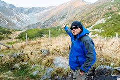 L'homme va à la montagne avec des bâtons pour le trekking dans un temps merveilleux d'automne photos stock
