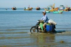 L'homme va par la mer sur le scooter chargé dans la perspective des bateaux de pêche Image stock