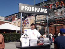 L'homme vend des programmes en dehors de stade de base-ball avant jeu Photo libre de droits