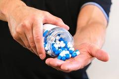 L'homme a versé une poignée de capsules de sports dans sa paume Réception avant la formation Augmentez la force et l'énergie Gros photographie stock