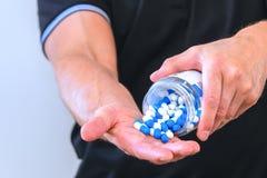 L'homme a versé une poignée de capsules de sports dans sa paume Réception avant la formation Augmentez la force et l'énergie Gros photo stock