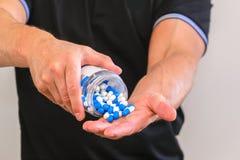 L'homme a versé une poignée de capsules de sports dans sa paume Réception avant la formation Augmentez la force et l'énergie Gros photos stock