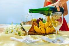 L'homme verse le champagne dans un verre sur un fond d'un plat avec le fruit Célébration sur la plage Photos stock