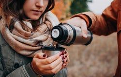 L'homme verse le thé chaud hors du thermos dans la forêt d'automne Image stock