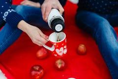 L'homme verse le thé dans une tasse avec une photo du coeur Les jeunes couples dans des chandails se reposent sur la couverture r Photos libres de droits