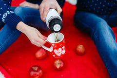 L'homme verse le thé dans une tasse avec une photo du coeur Les jeunes couples dans des chandails se reposent sur la couverture r Photographie stock libre de droits