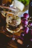 L'homme verse le vin blanc dans les verres Photographie stock