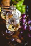 L'homme verse le vin blanc dans les verres Photos stock