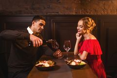 L'homme verse le vin dans un verre, couple dans le restaurant Photo libre de droits