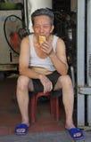 L'homme vietnamien s'assied sur un tabouret et mange du pain Image stock
