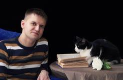 L'homme viril blanc à côté de la table où le chat se repose, se trouve un livre et une fleur de rose images libres de droits