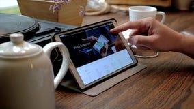 L'homme visite le site Web de l'iPhone 7 sur le PC de comprimé dans un café banque de vidéos