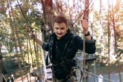 L'homme, vitesse s'élevante en parc d'aventure sont occupés à escalade ou passent des obstacles sur la route de corde, arborétum, photographie stock