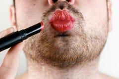 L'homosexuel barbu d'homme compose des lèvres avec le rouge à lèvres photo stock