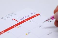 L'horaire de travail d'écriture de main sur le calendrier de bureau Images stock
