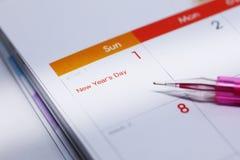 L'horaire de travail d'écriture de stylo sur le calendrier de bureau Image stock