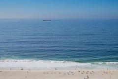 L'horizon nuageux et le brouillard au-dessus de la mer ondule, le fond naturel, le cargo rouge sur l'horizon, plage dans le premi Photographie stock