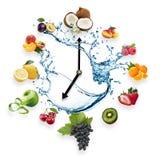L'horloge a arrangé des fruits sains éclaboussent par l'eau d'isolement sur W Photos libres de droits