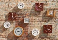 L'horloge est sur un mur de briques Temps différent photographie stock libre de droits