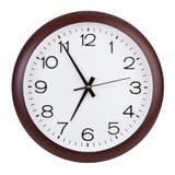 L'horloge ronde montre cinq minutes à sept Photo stock