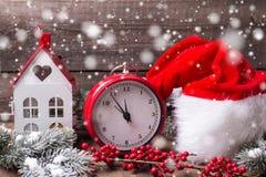 L'horloge rouge de vintage, chapeau de Santa, maison décorative, s'embranche fourrure Image libre de droits