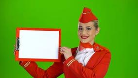 L'hostess alza una cartella rossa con un foglio di carta bianco Schermo verde archivi video