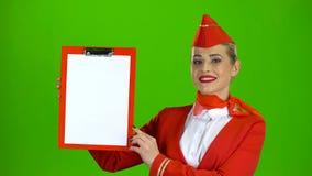 L'hostess alza una cartella rossa con un foglio di carta bianco Schermo verde stock footage