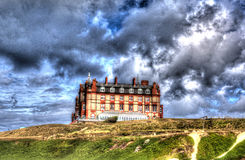 L'hotel Newquay Cornovaglia Regno Unito del promontorio dalla spiaggia di Fistral in HDR colourful luminoso con cloudscape Fotografie Stock Libere da Diritti