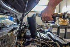 L'huile à moteur est versée dans un moteur de voiture images stock