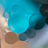 L'huile beige, grise, bleue de gradient se laisse tomber dans l'eau - fond abstrait photo libre de droits