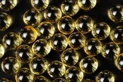 L'huile capsule le macro sur le fond noir Photographie stock libre de droits