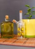 L'huile d'olive de deux bouteilles en verre se tient près d'une fleur sur un fond foncé Photographie stock libre de droits