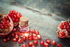 L'huile de grenade dans la bouteille et le grenat portent des fruits avec des graines image stock