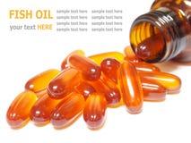 L'huile de poisson capsule le versement hors de la bouteille d'isolement sur le blanc Images stock