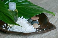 L'huile essentielle avec de la cire cosmétique granulée. Photos stock