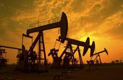 L'huile refoulent le coucher de soleil Photo stock