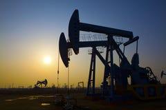 L'huile refoulent le coucher de soleil Photographie stock libre de droits